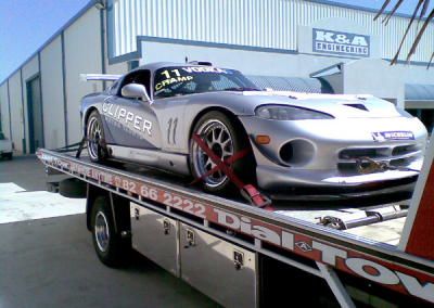 Clipper sponsored race car being towed with Dial-a-Tow's prestige car towing tilt truck