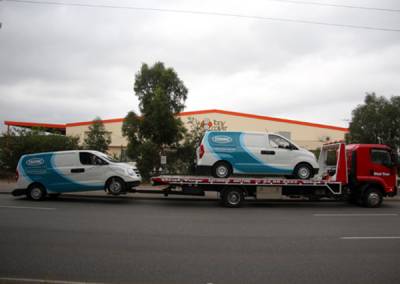 2 large vans being towed