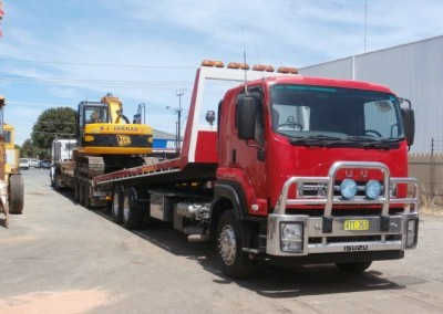 Our fleet's prized possession, the advanced Mac Excavator, towing heavy industrial machine