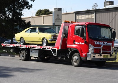A yellow Holden Monaro being towed from the service centre to it's owner's hoem