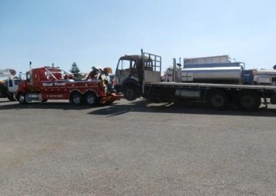A Mac low loader tilt truck transporting a heavy trailer truck