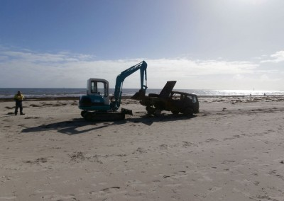 A front end loader with caterpillar tracks had to be used to access the vehicle to be recovered because of the soft sand
