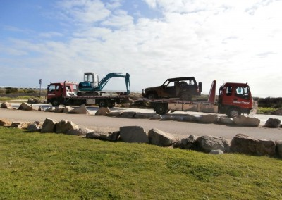 Two Dial-a-Tow trucks on-site at a beach, towing a broken down jeep and a forklift