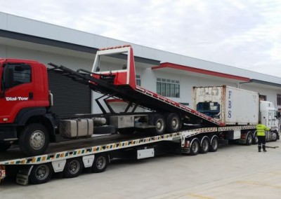Towing a shipping container with one of our state-of-the-art tilt trucks